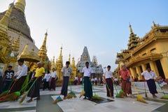 Un groupe de personnes balayent soudainement ensemble le plancher dans une longue file dans la pagoda de Shwedagon Photographie stock libre de droits