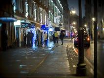 Un groupe de personnes cigarettes de tabagisme sur la rue à l'entrée à la barre photographie stock libre de droits
