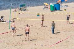 Un groupe de personnes, hommes et femmes jouant le volleyball de plage Image stock