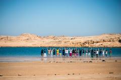 Un groupe de personnes se tenir se remet et se tenant près d'un lac bleu entouré par un désert Photographie stock