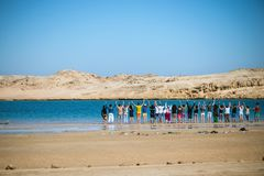 Un groupe de personnes se tenir se remet et se tenant près d'un lac bleu entouré par un désert Images libres de droits