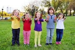 Un groupe de petits enfants avec des mains sales dans le jeu de peinture de couleur en parc Image stock