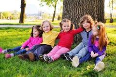Un groupe de petits enfants dans des vêtements colorés embrassant se reposer sur l'herbe sous un arbre en parc riant et souriant Photos stock