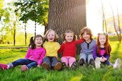 Un groupe de petits enfants dans des vêtements colorés embrassant se reposer sur l'herbe sous un arbre en parc riant et souriant Photographie stock libre de droits