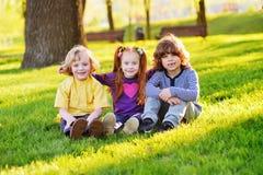 Un groupe de petits enfants dans des vêtements colorés embrassant se reposer sur l'herbe sous un arbre en parc riant et souriant Images libres de droits