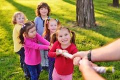Un groupe de petits enfants préscolaires jouent un conflit en parc image stock