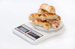 Un groupe de petits pains en croissant cuits au four frais sur une échelle numérique de cuisine Photos libres de droits