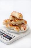 Un groupe de petits pains en croissant cuits au four frais sur une échelle numérique de cuisine Image libre de droits