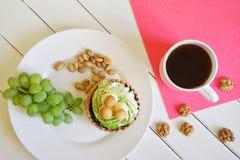 Un groupe de raisins, pistaches, noix attaquent avec du café noir sur un fond en bois blanc à côté d'une serviette rose Petit d?j photographie stock libre de droits