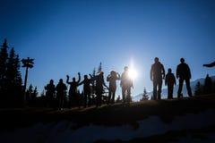 Un groupe de randonneurs sur une colline contre le soleil Image libre de droits