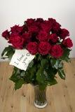 Un groupe de roses dans le vase en verre avec la carte d'amour Photo libre de droits