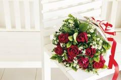 Un groupe de roses rouges sur la chaise en bois blanche Photographie stock