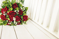 Un groupe de roses rouges sur le banc en bois blanc Photo libre de droits