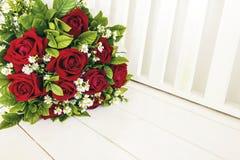 Un groupe de roses rouges sur le banc en bois blanc Photos stock