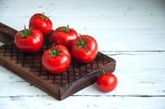 Un groupe de tomates fraîches au-dessus d'un conseil en bois sur un backgro blanc Photographie stock libre de droits