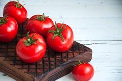 Un groupe de tomates fraîches au-dessus d'un conseil en bois sur un backgro blanc Photos libres de droits