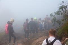 Un groupe de touristes descendant de la montagne un matin d'été dans un brouillard fort L'Indonésie, Bali, le volcan de Batur Image stock