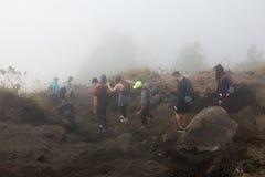Un groupe de touristes descendant de la montagne un matin d'été dans un brouillard fort L'Indonésie, Bali, le volcan de Batur Images libres de droits