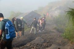 Un groupe de touristes descendant de la montagne un matin d'été dans un brouillard fort L'Indonésie, Bali, le volcan de Batur Photos libres de droits