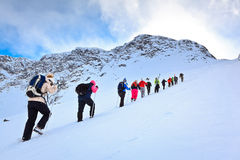 Un groupe de touristes vers le haut de la colline sur la pente de neige Photographie stock libre de droits