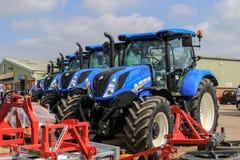 Un groupe de tracteurs bleus garés  Photographie stock