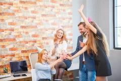 Un groupe des hommes et de femmes travaillant dans le bureau, mangeant de la pizza dans une humeur de fête Photos libres de droits