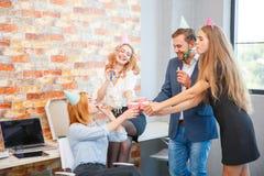 Un groupe des hommes et de femmes travaillant dans le bureau, mangeant de la pizza dans une humeur de fête Photos stock