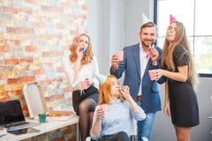 Un groupe des hommes et de femmes travaillant dans le bureau, mangeant de la pizza dans une humeur de fête Photographie stock