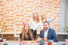 Un groupe des hommes et de femmes travaillant dans le bureau, mangeant de la pizza dans une humeur de fête Images stock