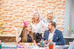 Un groupe des hommes et de femmes travaillant dans le bureau, mangeant de la pizza dans une humeur de fête Photo libre de droits