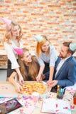 Un groupe des hommes et de femmes travaillant dans le bureau, mangeant de la pizza dans une humeur de fête Image libre de droits