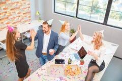 Un groupe des hommes et de femmes travaillant dans le bureau, mangeant de la pizza dans une humeur de fête Images libres de droits