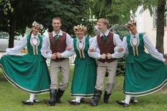 Un groupe des jeunes des costumes folkloriques lettons Image stock