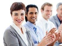 Un groupe divers d'affaires battant une présentation Photo stock