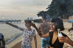 Un groupe divers d'amis appréciant des cierges magiques à la plage ensemble Image stock