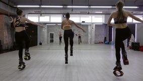 Un groupe femelle de trois jeunes, les filles sexy Kangoo saute dans le gymnase banque de vidéos