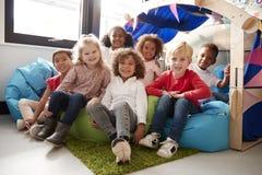 Un groupe multi-ethnique d'écoliers infantiles s'asseyant sur des fauteuils poire dans un coin confortable de la salle de classe, photographie stock libre de droits