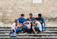Un groupe multi-ethnique de types ayant l'amusement causant sur les escaliers o Images stock