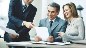 Un groupe réussi d'affaires discute un plan de travail utilisant un comprimé image libre de droits