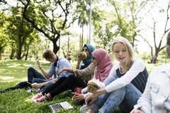 Un grupo de adolescentes diversos merienda en el campo en el parque Imagenes de archivo