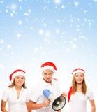 Un grupo de adolescentes en sombreros de la Navidad en un fondo nevoso Imagenes de archivo