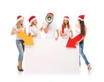 Un grupo de adolescentes en sombreros de la Navidad que señalan en un banne en blanco Imagen de archivo