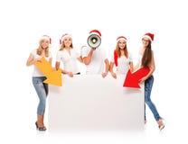 Un grupo de adolescentes en sombreros de la Navidad que señalan en una bandera Fotos de archivo