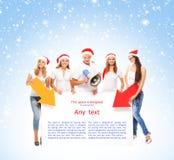Un grupo de adolescentes en sombreros de la Navidad que señalan en una bandera Imágenes de archivo libres de regalías