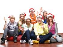 Un grupo de adolescentes felices en sombreros de la Navidad Imágenes de archivo libres de regalías
