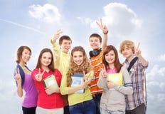 Un grupo de adolescentes felices que presentan en la hierba Foto de archivo libre de regalías