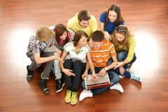 Un grupo de adolescentes jovenes que miran la computadora portátil Fotografía de archivo