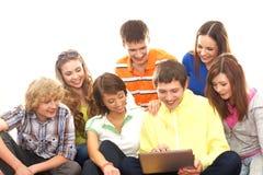 Un grupo de adolescentes jovenes que miran la computadora portátil Fotografía de archivo libre de regalías