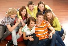 Un grupo de adolescentes jovenes que miran la televisión Fotos de archivo libres de regalías
