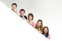 Un grupo de adolescentes jovenes que sostienen una bandera blanca Imagen de archivo libre de regalías